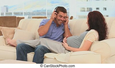 Future parents having fun with headphones in the living room