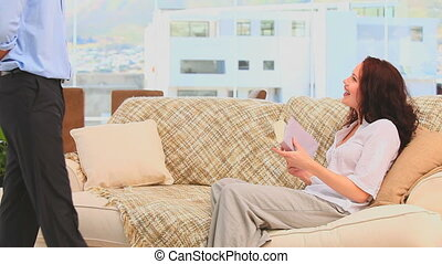 Man bringing a bunch of flowers to his wife on their sofa