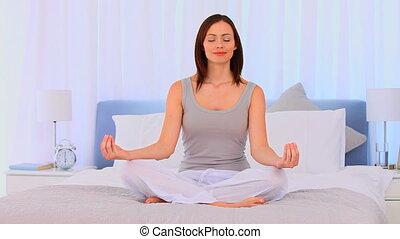 Good looking brunette doing yoga in the bedroom