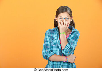 Child Covers Her Own Face - Giggling Latina child on orange...