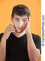 Young Man with Hand on Face - Young Mexican American man...
