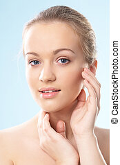 Skincare - Portrait of a beautiful blonde touching her face