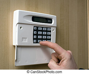 Setting an intruder alarm - Image of a hand setting a...