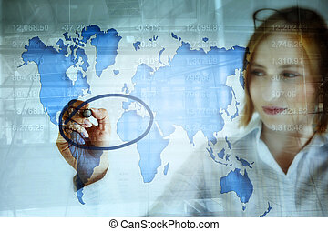 stock market and the world map - young business woman doing...