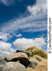 Rocks at the beach against a blue sky