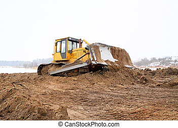 A yellow bulldozer working in the winter - bulldozer loader...