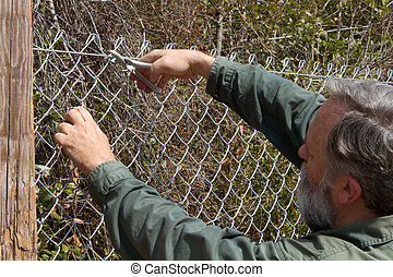 Building Fence - Man attaches hog ring to chain link fence...