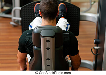 Man in gym on machine exercising - Man doing fitness...