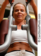 Woman in gym on machine exercising - Woman doing fitness...