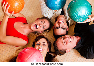 Friends bowling together - Group of four friends lying in a...