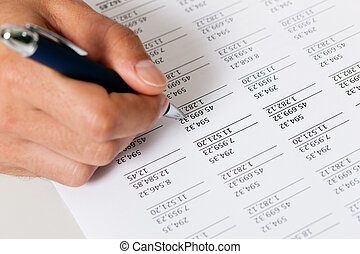 Accountant working on numbers - Man only hand to be seen,...