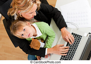 Businesswoman and mother is working at home - Family...