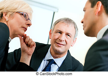 Business team discussing a project - Small business team in...