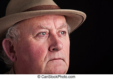 close up senior male wearing a hat