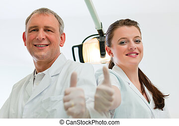 Dentists in their surgery looking at the viewer standing...