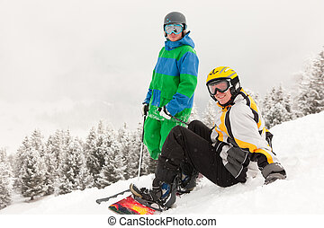 Skier and Snowboarder on mountain - Skier and snowboarder...