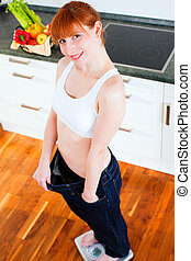 woman on diet with oversized pants - Woman standing on a...
