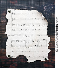 old musical notes hanging on wooden wall