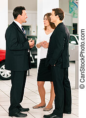 Couple with salesman at car dealer - Sales situation in a...