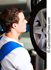 Car mechanic in workshop changing tire - Auto mechanic in...