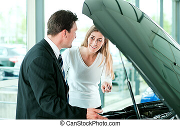 Woman buying car from salesperson