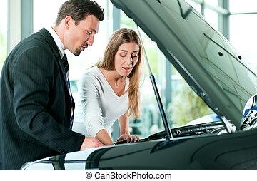 Woman buying car from salesperson - Woman buying a car in...