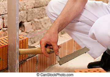 Bricklayer working on construction site - bricklayer laying...