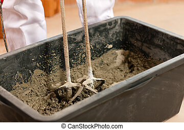 Construction worker mixing concrete or grout with a hand...