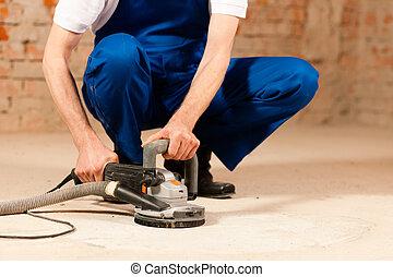 Sanding the cement floor - Construction worker working...