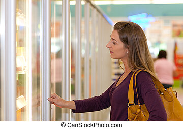 Woman in supermarket freezer section - Woman in a...