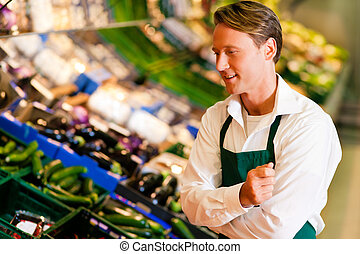 Man in supermarket as shop assistant - Shop assistant in a...