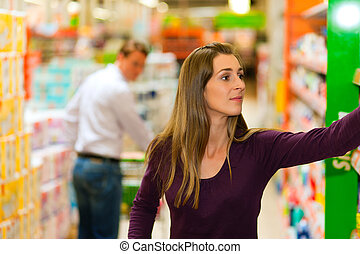 Man and woman in supermarket with shopping cart