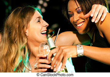 Friends having drinks in bar or club - Two female friends...