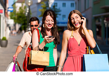 women downtown shopping with bags; a man is carrying the...