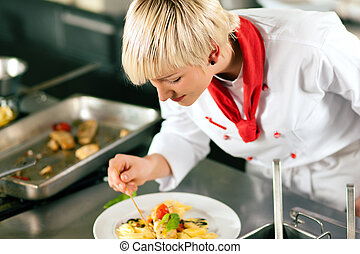 chef in restaurant kitchen cooking - Female Chef in a...