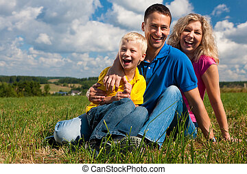 Family sitting on meadow?