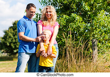 Family standing on meadow ?in summer