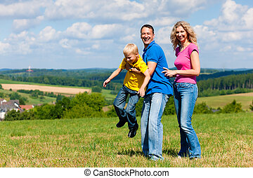 Family playing on meadow in summer