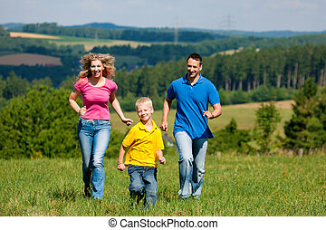 Family running on meadow in summer