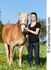 Teenage girl with horse - Teenage girl standing on a meadow...