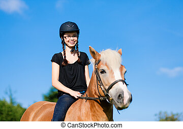 Teenage girl with horse - Teenage girl riding in summer with...