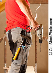 Construction worker with hand drill