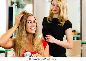 Woman at the hairdresser getting advise on her hair styling,...