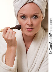 Beautiful blonde thirties caucasian woman doing makeup
