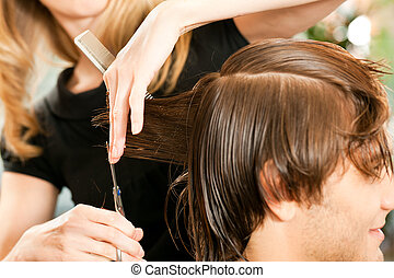Man at the hairdresser, she is cutting - close-up with...