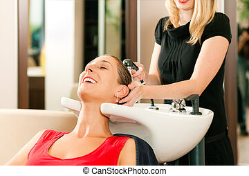 Woman at the hairdresser getting her hair washed and rinsed...