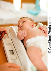 Baby on weight scale - Baby on a weight scale, her mother or...