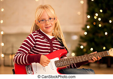 Girl with guitar in front of Christmas tree - Young child...