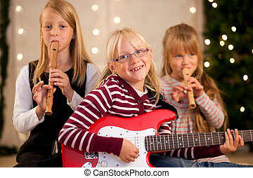 Children making music for Christmas - Young children with...
