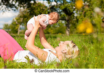 Mother playing with baby on meadow - Mother playing with her...